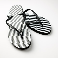 Pair of black and white stripe flip flops isolated on white background
