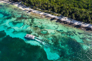 Fototapete - Aerial view from drone on tropical beach with palm trees and yacht with tourists floating in caribbean sea