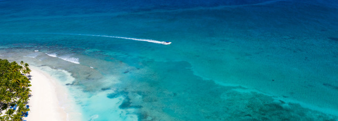 Fototapete - Aerial view on caribbean sea with floating boat