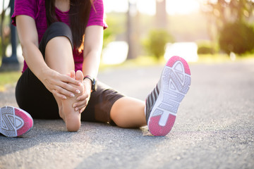 Young woman massaging her painful foot while exercising. Running Sport and excercise injury concept.