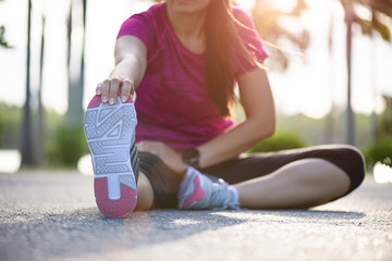Young fitness woman runner sit on the road stretching legs before run in the park. Outdoor exercise activities concept.