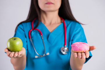 Healthy lifestyle, food and sport concept. Healthy versus unhealthy. Doctor woman hand holding donut and green apple.
