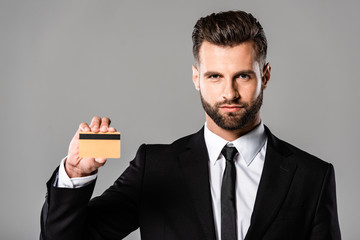 confident businessman in black suit holding credit card isolated on grey