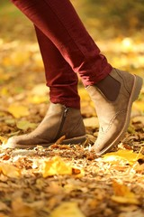 Autumn time. Autumn shoes .  legs in brown boots on yellow maple leaves. Fall season.