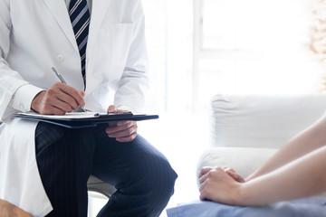 精神科医が患者との会話を記録している