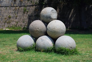 A pile of old stone cannonballs in the drained moat surrounding the medieval wall of Rhodes Old Town on the Greek island of Rhodes.