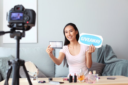Asian beauty blogger announcing giveaway while recording video at home