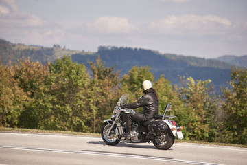 Side view of handsome bearded motorcyclist in helmet, sunglasses and black leather clothing riding cruiser motorbike along narrow asphalt path on sunny summer day.