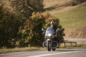 Bearded handsome motorcyclist in helmet, sunglasses and black leather clothing riding cruiser motorbike along empty asphalt road on bright sunny day.
