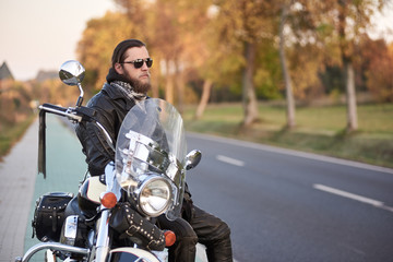 Handsome bearded biker in black leather clothing and dark sunglasses sitting on motorcycle on clean paved roadside, on background of empty straight asphalt road and vintage trees golden bokeh foliage.