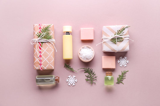 Christmas gift boxes and products for spa treatment on color background