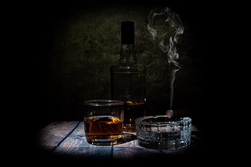 glass of wihisky and cigar on black background