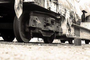 Old freight train locomotive wagon, close-up of the wheels, on track line covered with tarpaulin.  With colour toning.