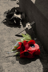 Poppy wreath,  with selective colour,  on the base of a war memorial honouring Remembrance Day.  With sepia toning