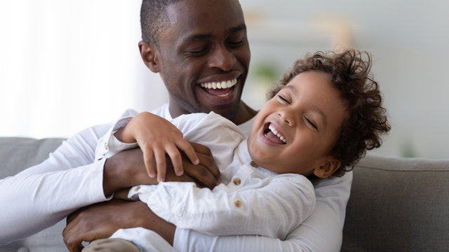 Happy black father tickling african kid son laughing cuddling together