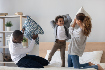 Happy mixed ethnicity parents son playing pillow fight on bed