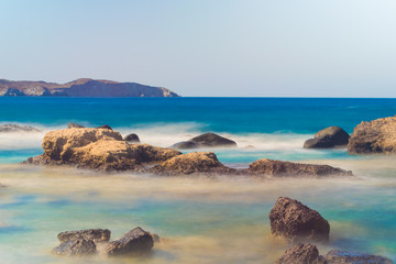 A rocky beach with turquoise crystal clear waters near Mandrakia village in Greece- long exposure (ND filter)