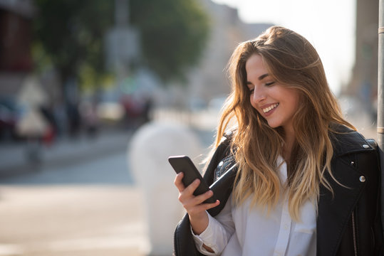 Pretty girl looking at mobile screen and smiling