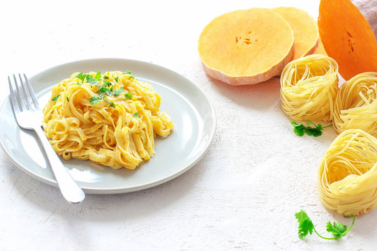 Pumpkin alfredo fettucine pasta in a ceramic plate on white background with fresh raw butternut squash slices. Autumn meal for lunch.Butternut squash recipe.Space for copy and text.Fettuccine pasta