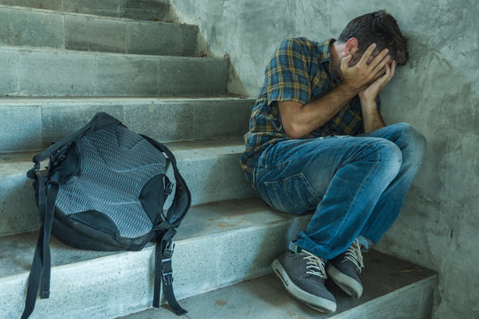 Campaign vs homophobia with young sad and depressed college student man sitting on staircase desperate victim of harassment suffering bullying and abuse