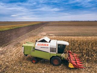 Claas combine harvester working on corn field