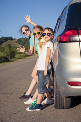 Happy brother and his two sisters are standing near the car at the day time.