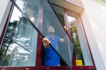 Fototapeta worker installing mosquito net wire screen on plastic pvc window obraz