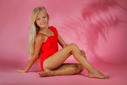 cute little baby girl in a red swimsuit posing on a pink background. summer time