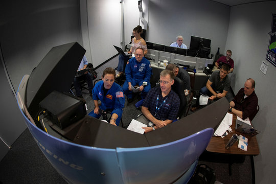 NASA commercial crew astronauts Nicole Mann and Mike Fincke and Boeing astronaut Chris Ferguson run through scenarios in a simulation cockpit of the Boeing Starliner spaceship at the Johnson Space Center in Houston