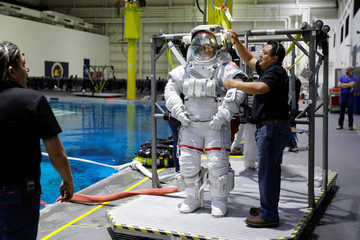 NASA Commercial Crew astronaut SunitaWilliams is helped to get into her space suit at NASA's Neutral Buoyancy Laboratory (NBL) training facility near the Johnson Space Center in Houston