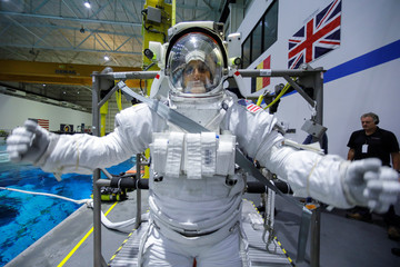 NASA Commercial Crew astronaut SunitaWilliams is helped to get into her space suit at NASA's Neutral Buoyancy Laboratory (NBL) training facility near the Johnson Space Center in Houston,