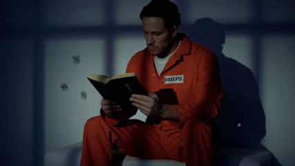 Imprisoned religious male reading bible, convicting in sins, feeling guilty