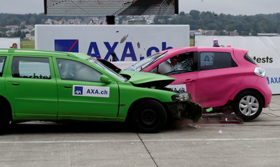 A Renault Zoe electric car (R) collides with an oncoming Volvo V70 car in a controlled crash test from insurer AXA in Duebendorf