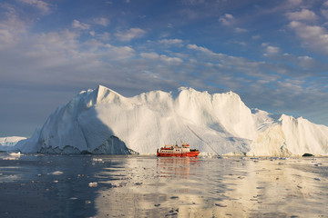 Foto op Aluminium Arctica A small boat among icebergs. Sailboat cruising among floating icebergs in Disko Bay glacier during midnight sun Ilulissat, Greenland. Studying of a phenomenon of global warming Ices and icebergs