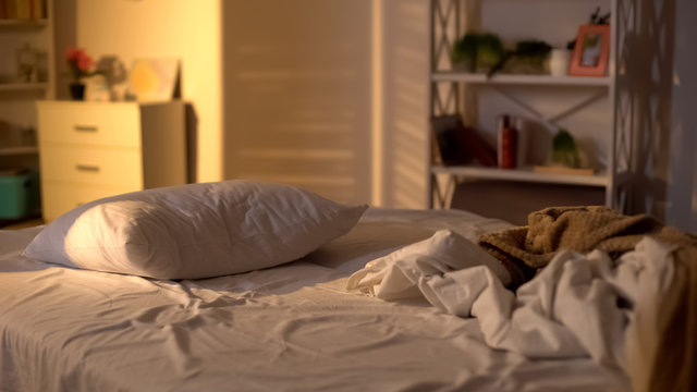 Messy bed, white pillow with blanket lying on bed unmade, oversleeping concept