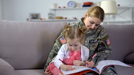 Little cute girl and US soldier mother drawing in coloring book at home, relax