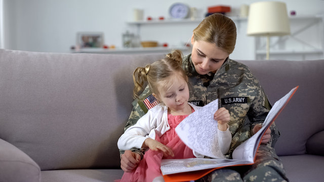 Mom in military uniform looking at drawings in coloring book together, leisure