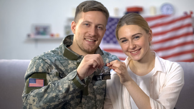 Cheerful US soldier and wife showing apartment keys, military service reward