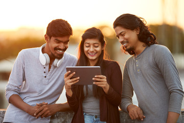 Cheerful young Indian friends playing in digital tablet