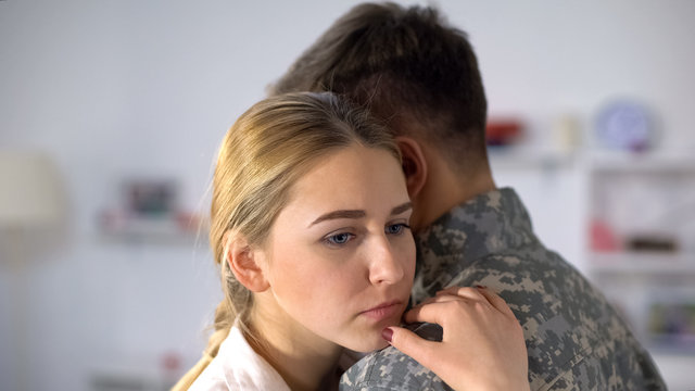 Sad girlfriend hugging male soldier, farewell before military service depression