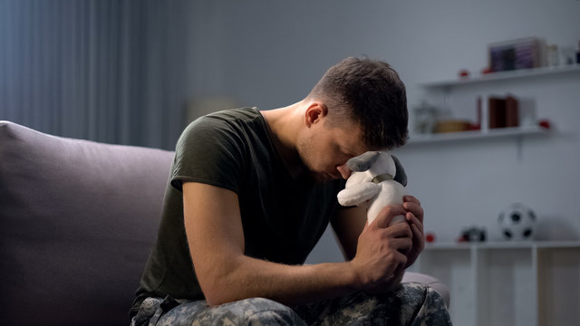 Melancholic male soldier holding toy dog, missing child after divorce, lonely