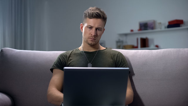 Male soldier typing on laptop pc at home, communication concept, military app