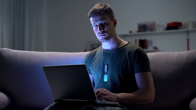 Male soldier typing on laptop pc, day and night psychological online support