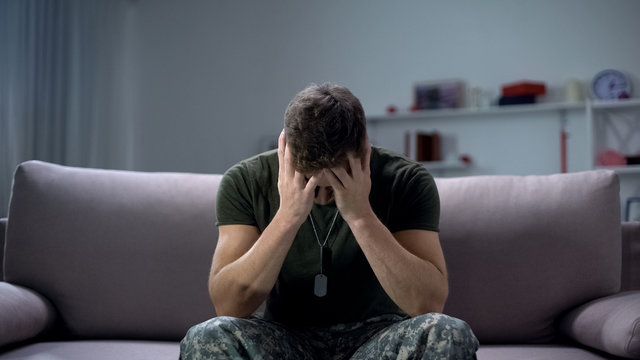 Nervous male military suffering depression, sitting alone at home, PTSD concept