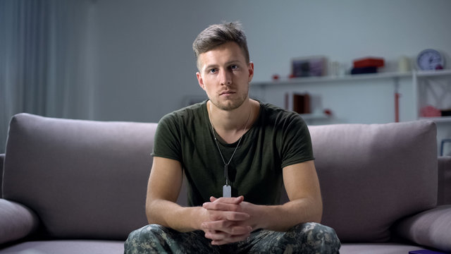 Sad male military sitting on sofa and looking at camera, psychological trauma