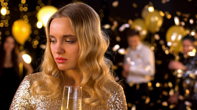 Sad blond woman feeling lonely at party, dancing people on background, offence