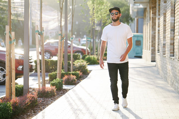 Fototapeta Hipster handsome male model with beard wearing white blank t-shirt and a baseball cap with space for your logo or design in casual urban style obraz