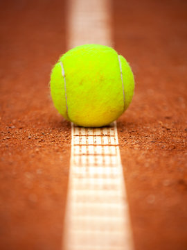 A yellow tennis ball lies on the clay court.