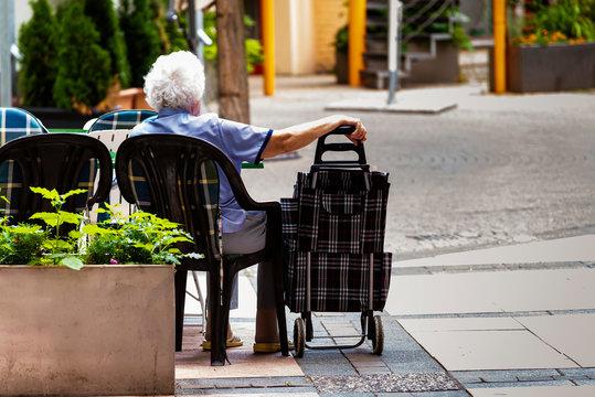 Sitting Grandma, A grandma is sitting on a chair, sitting grandma and a shopping trolley