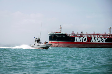 A boat of the Iranian Revolutionary Guard sails near to Stena Impero, a British-flagged vessel owned by Stena Bulk, at undisclosed place in Bandar Abbas port